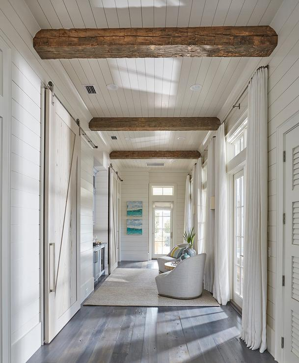 Hallway Boasts Rustic Wood Beam Ceiling As Well A Wall Of French Doors