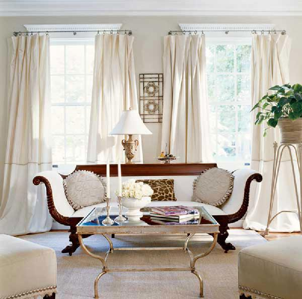 Glamourous living room French settee mirrored cocktail table and white silk drapes