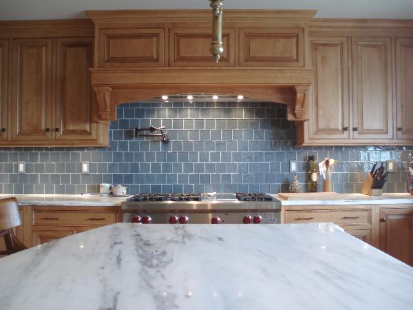 Tile Maple kitchen cabinets, marble countertops, pot filler and blue