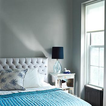 gray bedroom with gray walls white tufted headboard blue glass lamp