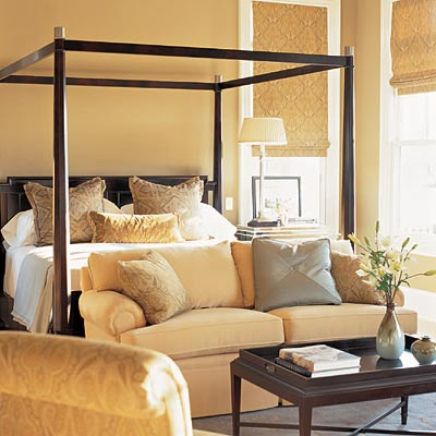 Master Bedroom With Black Canopy Bed And Small Sitting Area Love The Bamboo  Roman Shades And Wood Tray Coffee Table! Gold Yellow Paint Wall Color! Gold  ...