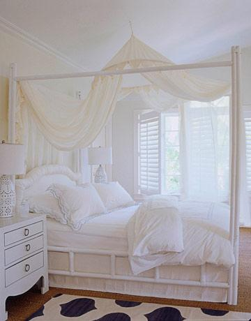 Romantic white bedroom Love the canopy bed, white bedding, glossy white  lacquer nightstand, white lamp, blue & white rug and soft creamy yellow  ivory walls.