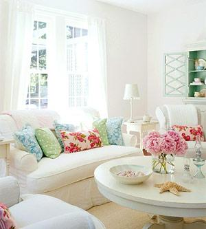 bright white color fun living room white sofas colorful pillows white pedestal coffee table white sheers and sisal rug