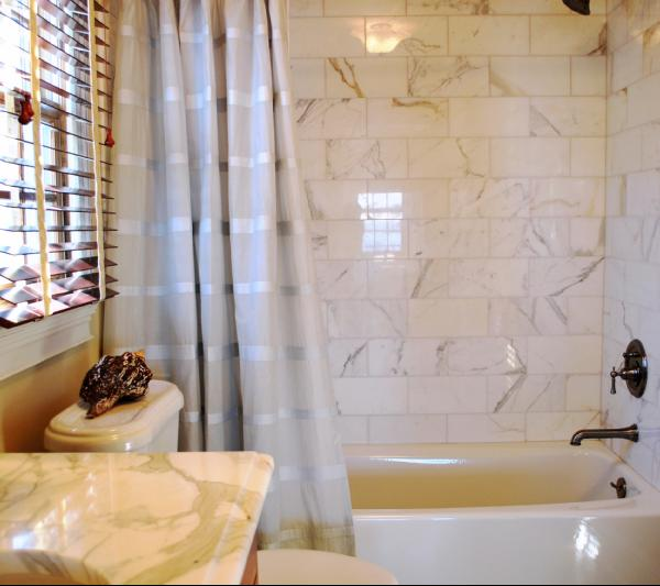 Stunning Bathroom Featuring Calcutta Gold Marble Shower Tiles Paired With Antique Nickel Fixtures And A Vanity Top