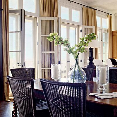 Coastal Dining Room Design With White French Doors Yellow Silk Drapes Farmhouse Table And Black Chairs