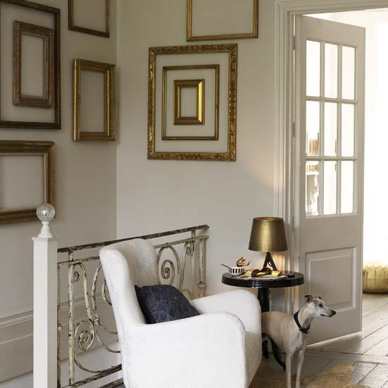 Gorgeous entrance foyer design with white chair round black pedestal table brass table lamp gray rustic wood floors gold gilt empty frames gallery and