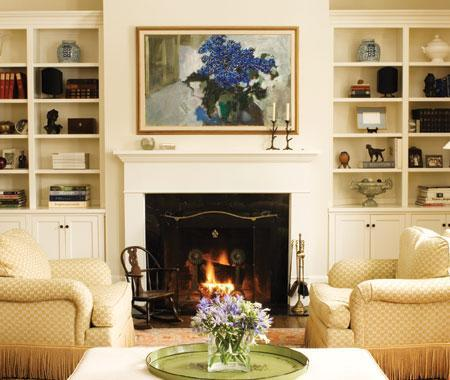 Beautiful built-ins next to the fireplace Rolled arm chairs, fireplace and  built-ins cabinets and bookcases.