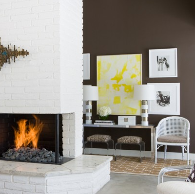 Yellow & chocolate brown living room design with white brick fireplace