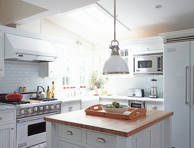 Clean Crisp White Kitchen With Butcher Block Island Countertop Carrara Marble Countertops Yoke Pendant Cabinets