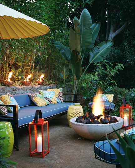 and lime green garden stools, red hurricane lanterns and fire pit