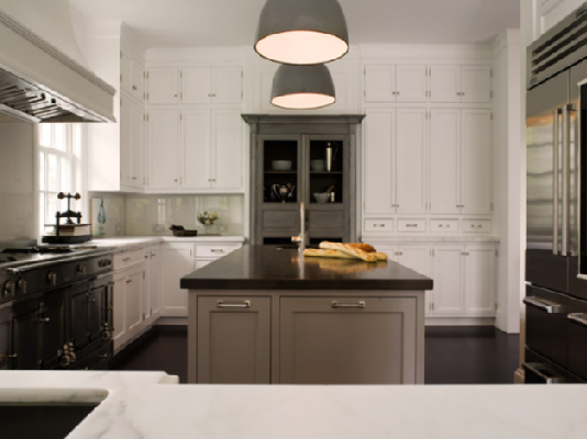 White kitchen cabinets and gray kitchen island and antique armoire