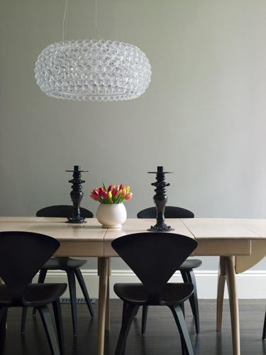 modern dining room design with modern dining table gray green walls paint color black cherner side chairs and bulle pendant chandelier