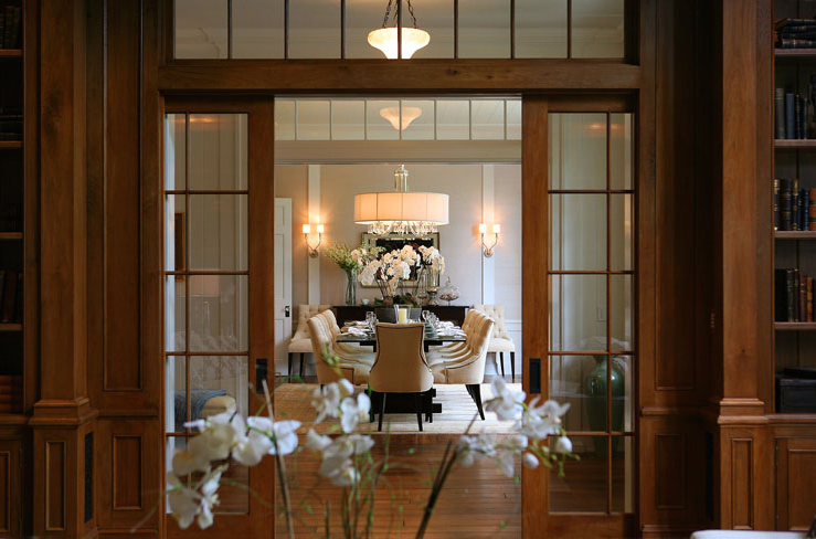 Beautiful Dining Room Design With Glass Pocket Doors Transom Windows Tufted Ivory Chairs Nailhead Trim And Crystal Chandelier