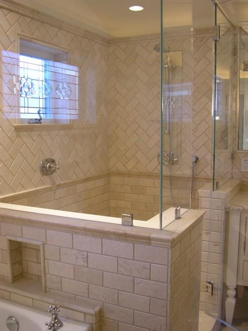gorgeous bathroom design with frameless glass shower with stone tiles in a chevron herrinbone pattern