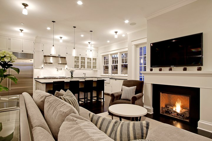 Chic Comfy Cozy Open Living Room Kitchen Design With Gray Sofa Striped Gray Pillows Fireplace Tv And Brown Velvet Chair