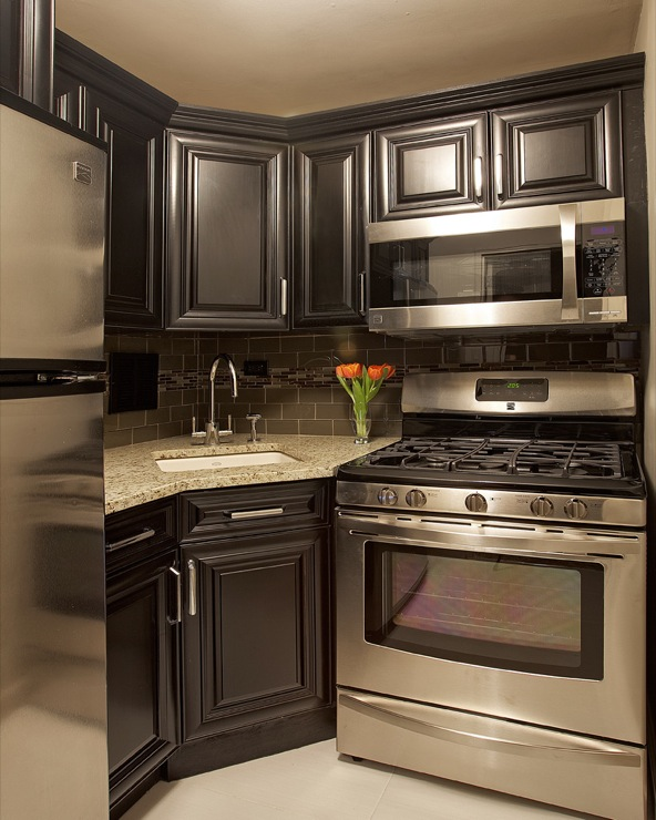 The black satin custom cabinets, stainless steel appliances, gold