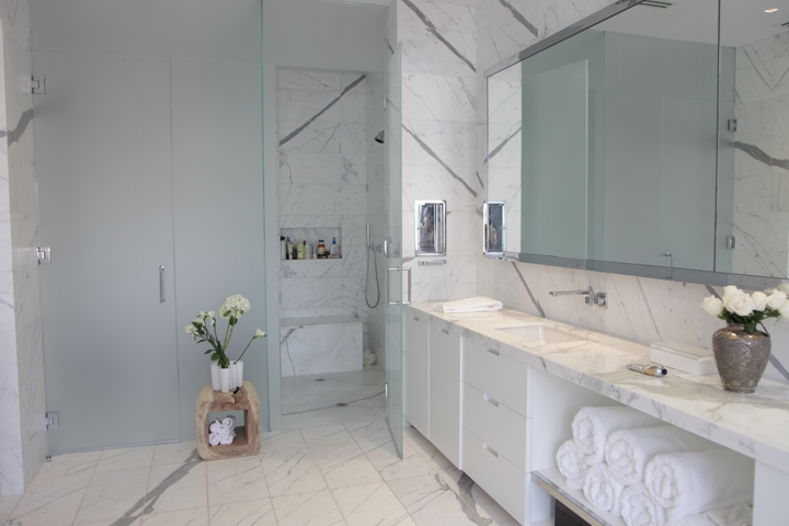 chic modern bathroom design with white bathroom vanity cabinets calcutta gold marble countertop marble tiles floor and tempered glass frameless shower