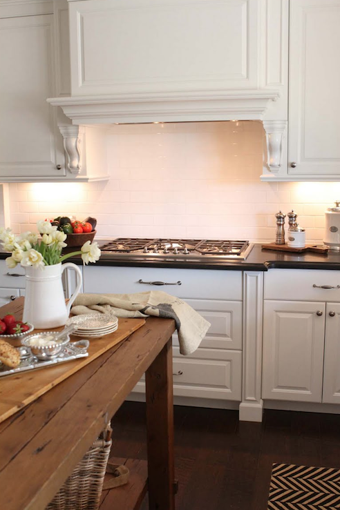 Wonderful kitchen remodel with reclaimed wood kitchen island, beveled honed  black granite counter tops, white kitchen cabinets, subway tiles backsplash  and ...