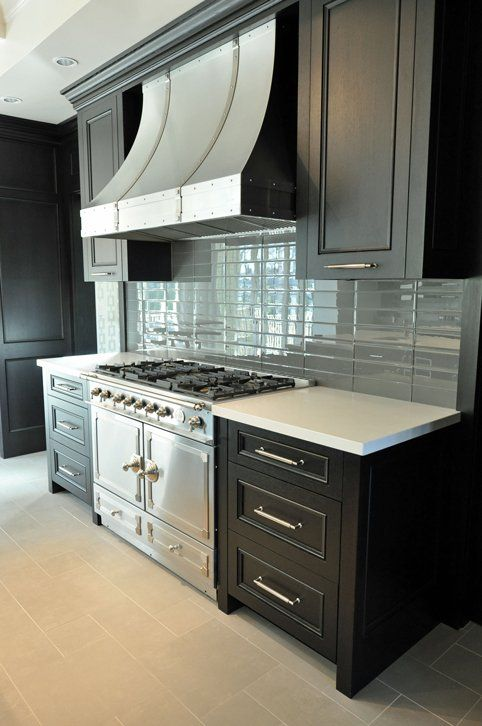 Gorgeous Kitchen Design With Ebony Kitchen Cabinets, La Cornue Range,  French Curve Range Hood And Blue Glass Tiles Backsplash.