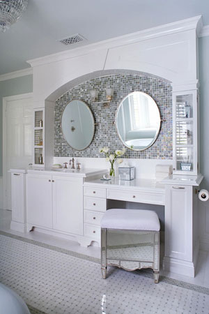mosaic backsplash behind mirrors crisp white cabinetry and carrara mosaic floor make up vanity