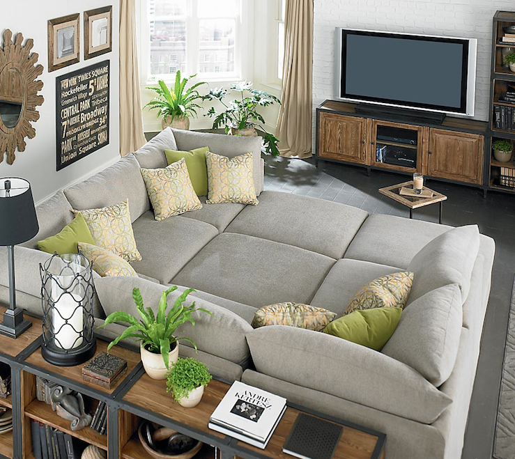huge gray bassett beckham pit sectional sofa green pillows industrial bookshelves subway sign wood sunburst mirror exposed brick wall painted white and