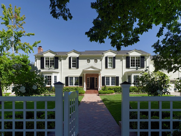 Colonial Home Exterior Design With White Lattice Fence Brick Pathway Black Shutters Gray Shingles And Attached Garage