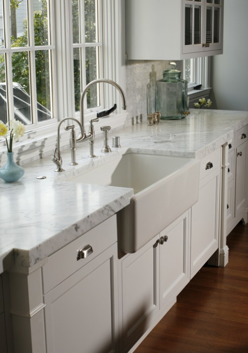 gorgeous kitchen design with white kitchen cabinets with marble counter tops polished nickel gooseneck bridge kitchen faucet farmhouse sink and marble