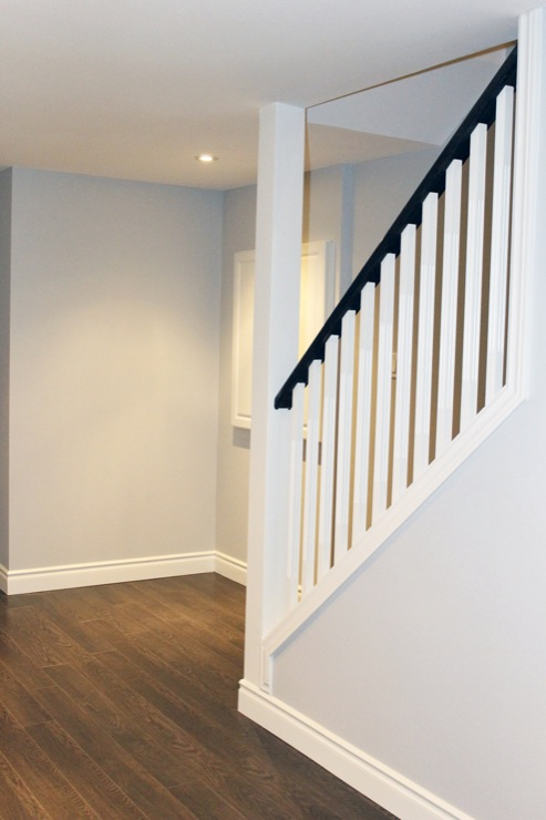 White Basement Staircase With Black Handrail