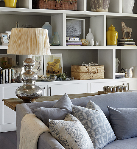 Chic Living Room With White Built In Cabinets Backs Of Shelves Painted Taupe Gray Yellow Ginger Jars Hammered Metal Gourd Lamp And Blue Sofa