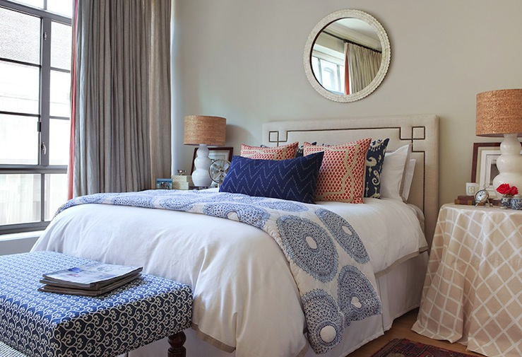 Light gray walls paint color serena lily octavia headboard capiz scalloped round mirror blue ikat pillows skirted table nightstand white gourd lamps