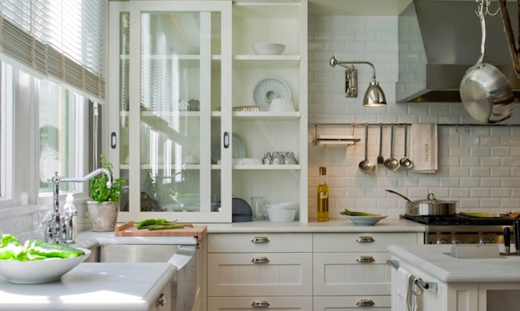 beautiful Sliding Glass Kitchen Cabinet Doors #4: Glass-front sliding kitchen cabinets in off-white ivory, light gray honed  quartz countertops, subway tiles backsplash and stainless steel apron sink.