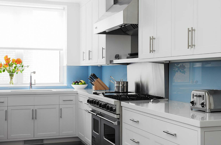 kitchen cabinets with white quartz countertops and blue backsplash