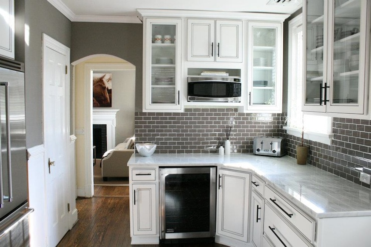 marble countertop wine fridge and gray glass subway tile backsplash