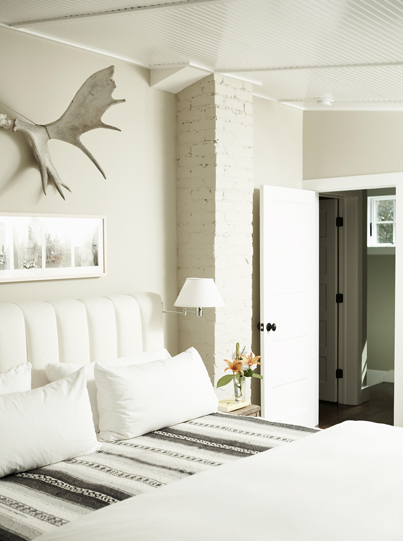 Cool bedroom with greige walls paint color, white headboard, white & gray  bedding, swing arm wall sconces and glossy white beadboard ceiling.