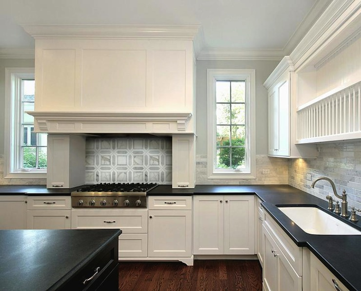 white kitchen cabinets, black kitchen island, honed black granite
