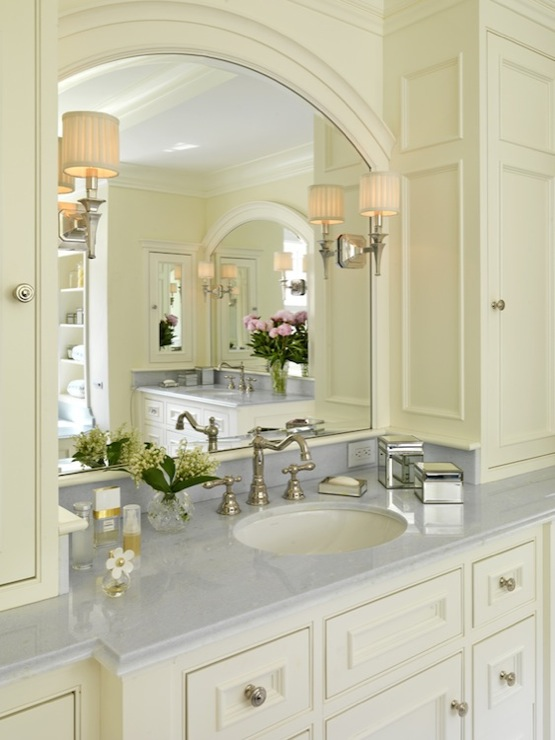 bathroom with twin cream bathroom vanities with marble countertops