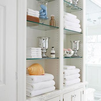 bathroom storage with creamy white built in linen cabinets with marble