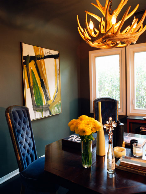 Glam Dining Room With Bold Black Walls Paint Color Faux Antlers Chandelier Abstract Art Royal Blue Velvet Tufted Chairs Octagon Wood Table And