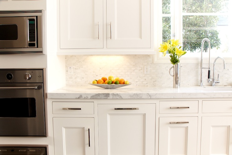 white kitchen cabinets with marble countertops and marble mosaic tiles