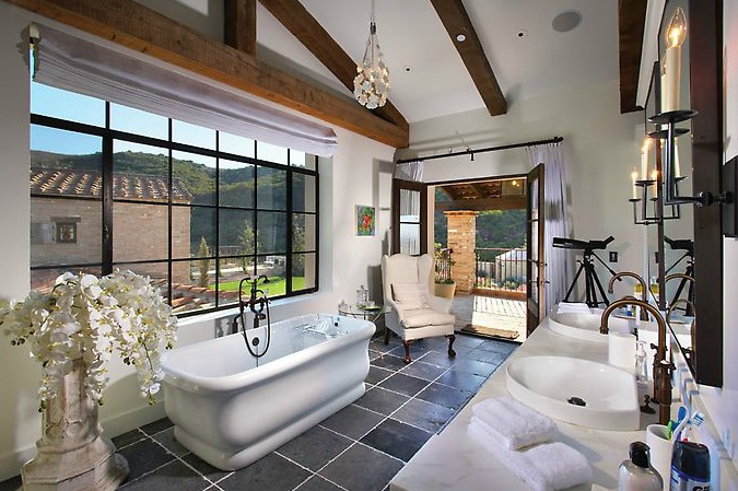 gorgeous ensuite with slate tiles floor tub french doors wingback chair rustic wood beams double bathroom vanity and espresso stained