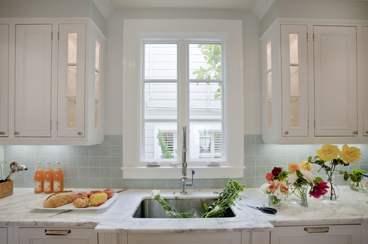 With White Glass Front Raised Panel Kitchen Cabinets With Marble Countertops Gray Walls Paint Color And Blue Square Glass Stacked Tiles Backsplash