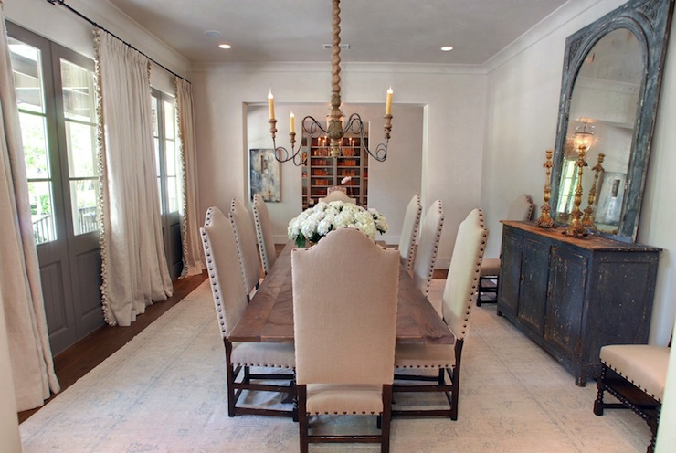 French Dining Room With Wall Of Gray Doors Covered In Ivory Linen Drapes Pom Tassel Fringe Camelback Chairs