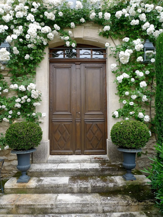 Whimsical Front Entrance With Solid Wood Doors, Stone Pavement And Gray  Topiary Urns.