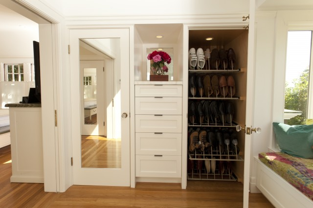 White mirrored shoe closets flanking built-in dresser.