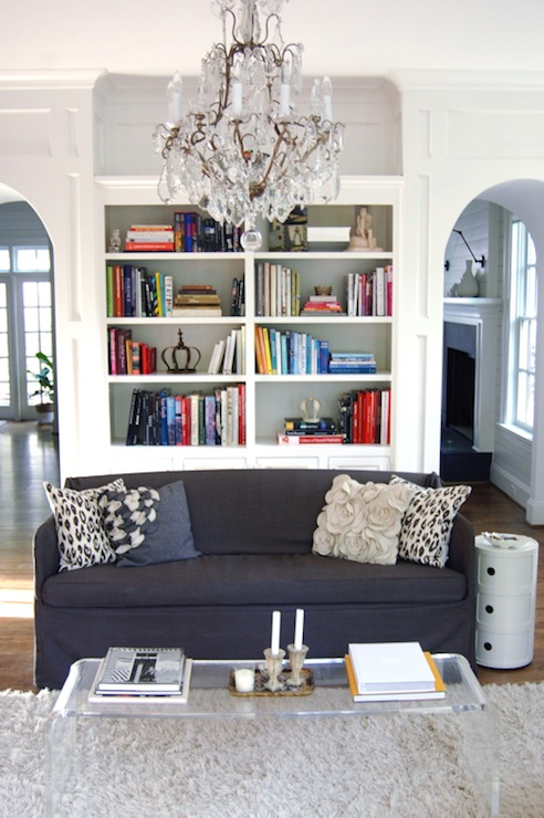 Chic Living Room With White Built Ins Navy Blue Sofa Gray Flower Pillow Kartell Componibili Round Tower CB2 Peekaboo Clear Coffee Table And Ivory Shag