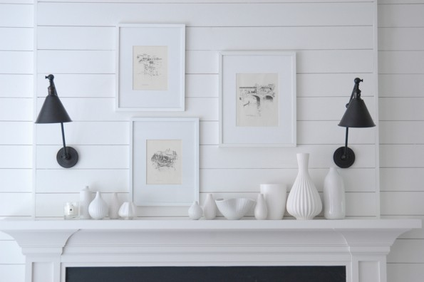 gorgeous fireplace mantel vignette with white groove walls black sconces collection of white vases and art in white gallery frames