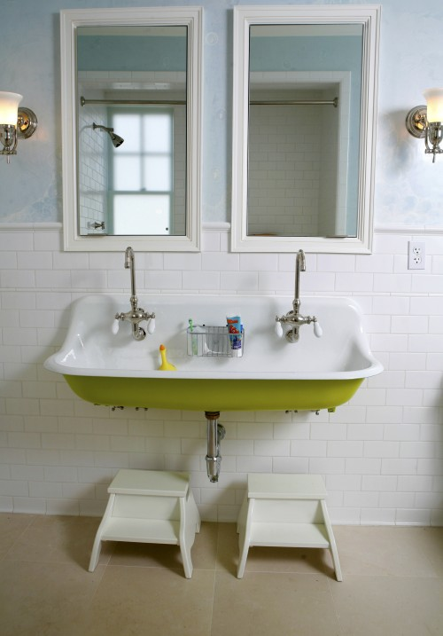 stools under kohler brockway sink painted green accented with dual faucets and white lacquer mirrors and blue walls paired with subway tile backsplash