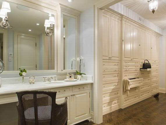 Ivory Built In Vanity With White Marble Top Paired With Cane Vanity Chair  Next To Walk In Closet Featuring Floor To Ceiling Ivory Cabinets.