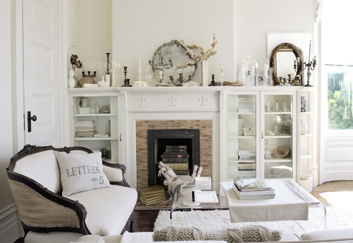 Chic Elegant Living Room With French Settee Accented Vintage Pillows CB2 Peekaboo Clear Coffee Table Over White Wool Rug And Fireplace Flanked By