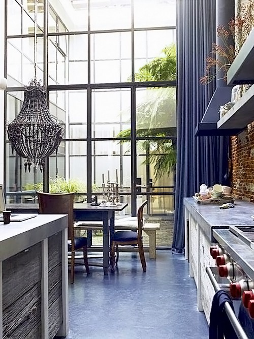 Kitchen With High Ceiling Exposed Brick Walls And Purple Curtains On Floor To Steel Windows